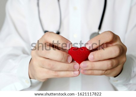 Cardiology and health care, doctor holding red knitted heart in hands. Concept of cardiologist, blood donation, treatment of heart disease in the clinic, diagnosis with stethoscope