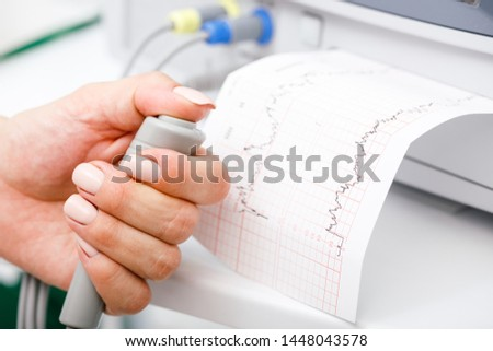 Cardiotocograph machine aka Electronic Fetal Monitor (EFM) recording the fetal heartbeat and the uterine contractions during pregnancy. Cardiotocography (CTG) monitoring concept Stock photo ©