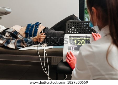 Cardiotocography. Pregnant woman sitting in clinic performing monitoring. Recording fetal heartbeat and uterine contractions during pregnancy. Stock photo ©