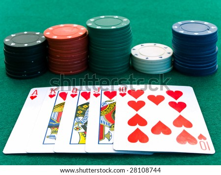 cards and a few color chips on the playing table in the casino
