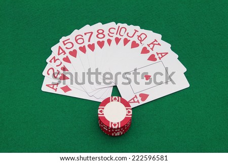 Cards and casino chips on green casino table