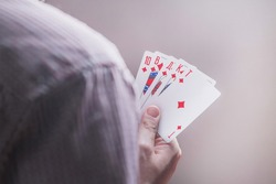 cards in the hands of a man with a combination of royal flush. Poker