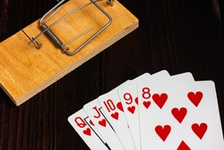 Cards on a wooden table, in the background a mousetrap. Poker hand royal flush.