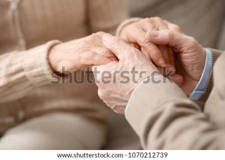 Care and affection. Close up of hands of pleasant aged people being held together while showing the affection #1070212739