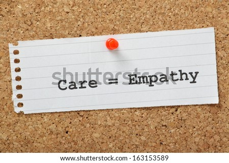 Care equals Empathy typed on a scrap of paper and pinned to a cork notice board. When working in the care profession or caring for someone at home, empathy is key to providing the best support.