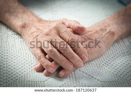 Care is at home of elderly. Old people holding hands. Closeup. Elderly man
