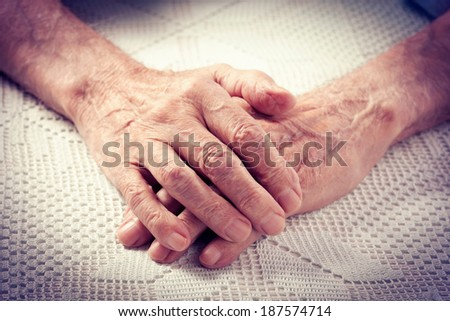 Care is at home of elderly. Old people holding hands. Closeup. Elderly man.