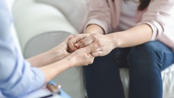 Care, trust, professionalism concept. Close up of therapist holding female patient hands, comforting her client, panorama with copy space