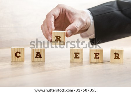 Career adviser assembling the word career with six wooden cubes  in a conceptual image of personal guidance towards self realization. #317587055