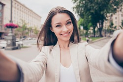 Carefree and happy, sunny spring mood. Charming young lady is making selfie on a camera. She is wearing formal wear, smiling, while on a walk in town outdoors