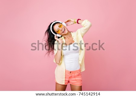 Carefree asian woman in summer clothes singing favorite song with happy face expression. Indoor portrait of fascinating hispanic girl in yellow jacket having fun during dance in studio.