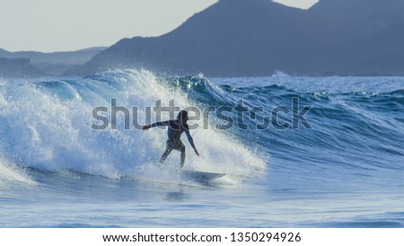 Carefree athletic male tourist surfing the big tube waves in sunny Fuerteventura. Cheerful young man in a black wetsuit skilfully carving the breaking blue waves in the picturesque Canary Islands. #1350294926