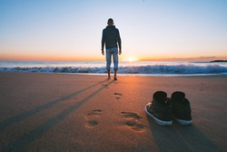 Carefree barefoot man going to the sea or the ocean without shoes on sunset. Concept of freedom. Enjoyment and harmony
