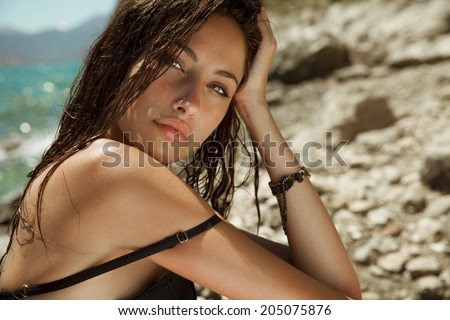 Carefree beautiful brunette with wet look & long hair on the beach. Natural woman beauty. Toned in warm colors. Copy space for your text. horizontal shot, outdoors