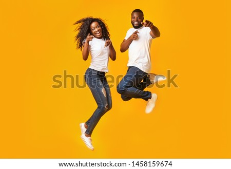 Carefree Black Millennial Man And Woman Are Jumping In The Air, yelllow background #1458159674