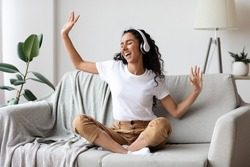 Carefree brunette woman listening to music and singing, using headphones, sitting on couch in living room, copy space. Happy young lady with closed eyes enjoying music, home interior