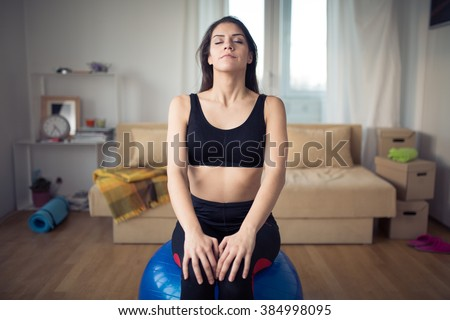 Carefree calm woman meditating.Enjoying peace and serenity.Living room for after work relaxation and meditation.Having a deep breath.After work out relaxation of muscles and breathing exercises