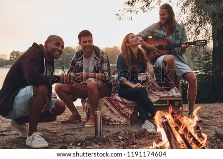 Carefree camping. Group of young people in casual wear smiling while enjoying beach party near the campfire
