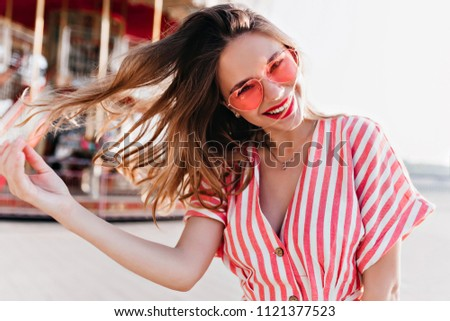 Carefree caucasian lady playing with her hair during photoshoot near carousel. Excited beautiful girl expressing good emotions in amusement park.