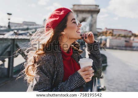 Carefree caucasian woman in red hat enjoying city views in warm windy day. Outdoor photo of cute female tourist in trendy earrings drinking coffee on embankment in european town.
