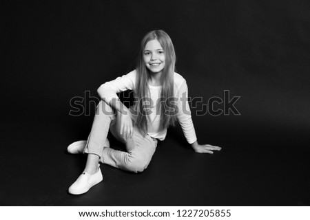 Carefree childhood. Girl long hair cute smiling face relaxing, black background. Child girl carefree enjoy childhood. Model young posing studio. Take advantage carefree childhood, copy space.