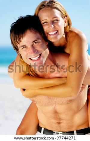 carefree couple embrace and enjoy some summer beach loving on a tropical island