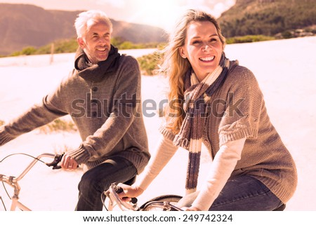 Carefree couple going on a bike ride on the beach on a bright but cool day