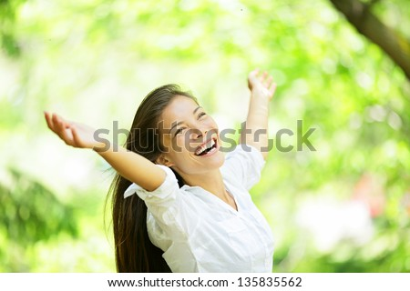 Carefree elated cheering woman in spring or summer forest park full of hope and vitality. Multiracial girl raising her arms up smiling happy. Mixed race Asian Caucasian female model.
