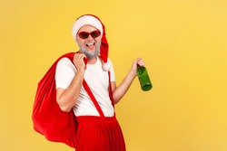 Carefree elderly man in sunglasses and santa claus costume with big red bag holding bottle with alcohol and smiling at camera, bad habits. Indoor studio shot isolated on yellow background