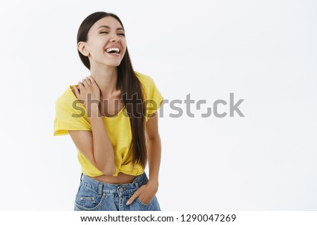 Carefree enthusiastic asian woma having fun laughing out loud over funny joke having amusing time looking right touching neck chuckling being entertained in awesome company posing in stylish outfit