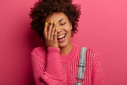 Carefree ethnic girl cannot stop laughing, keeps hand on face, has cheerful face, smiles positively, has good sense of humor, expresses happiness, wears knitted jumper, poses over pink background