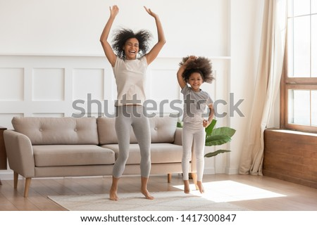 Carefree funny african family young mom having fun with cute little kid girl jump dancing in living room, happy mixed race mother with small child daughter laugh do morning exercise together at home
