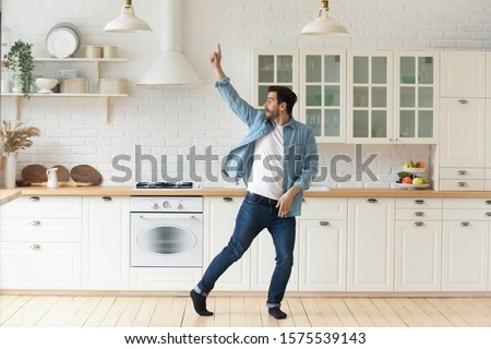Photo of Carefree funny young man having fun dancing alone in modern kitchen interior, active happy funky single guy enjoying silly movements dance standing at home listening music celebrating freedom concept