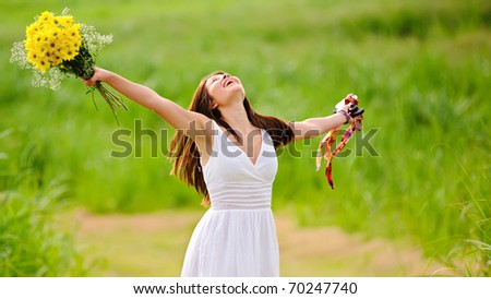Carefree girl is happy in field with flowers