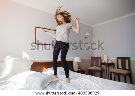 Carefree girl jumps on the bed while listening pop music, pop music fan girl