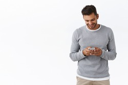 Carefree good-looking boyfriend staying touch with girlfriend abroad watching funny video-message in smartphone app, holding mobile phone gazing satisfied display, standing white background