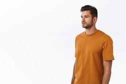 Carefree good-looking modern hipster guy with beard in brown t-shirt, standing half-turned with spaced-out casual expression, looking left, posing white background no emotions, urban people concept.