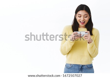 Carefree happy girl beating friends score in cool new mobile game, holding smartphone horizontally, playing online racing or shooter, smiling amused while standing against white background