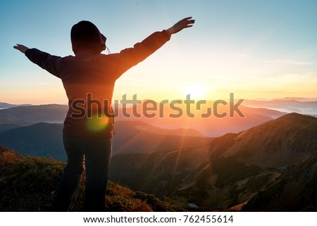 Carefree Happy Traveler Woman Enjoying Nature on top of mountain cliff with sunrise. Freedom concept. Len flare effect. Sunbeams. Enjoyment.                 #762455614