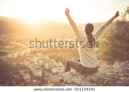 Carefree happy woman sitting on top of mountain edge cliff enjoying sun on her face raising hands in sunlight rays.Enjoying nature sunset.Freedom.Enjoyment.Relaxing in mountains at sunrise.Daydreaming