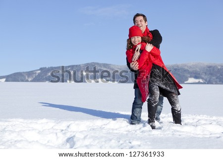 Carefree happy young couple having fun together in snow in winter