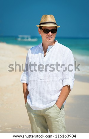 Carefree happy young man in sunglasses and hat on the sunny coast with the blue sea and boat on background