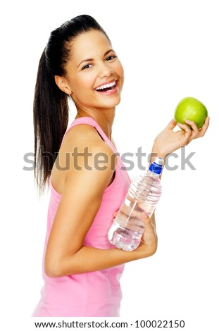 carefree healthy hispanic woman with apple and water smiling with cheerful confidence isolated on white