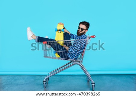 Carefree hipster fun. Side view of cheerful young man sitting in shopping cart with bright skateboard over colorful wall