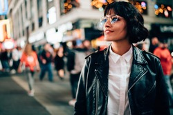 Carefree hipster tourist in optical spectacles for provide eyes protection enjoying evening walk in New York, attractive Caucasian woman dressed in trendy jacket looking around on Manhattan