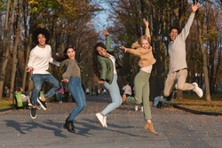 Carefree international students jumping in the air, having fun in park