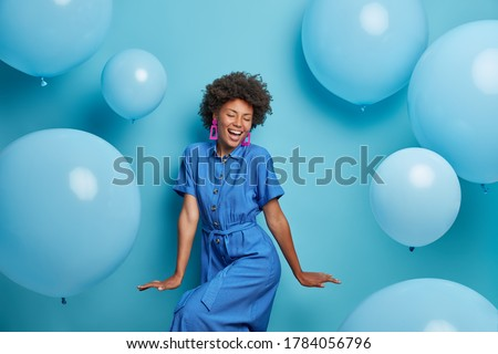 Carefree joyful curly woman dances happily, dressed in blue dress, chills at party around inflated helium balloons, feels playful, enjoys favorite holiday, has upbeat festive mood. Moment of joy