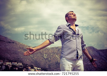 Carefree man enjoying in freedom with arms outstretched. Below view of man breathing fresh air with eyes closed.