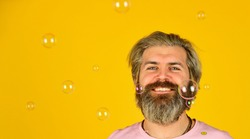 carefree man with bubble blower. happy hipster in playful mood. Fall into childhood. feeling childish and childlike. real happiness. april fools day. bearded man blowing soap bubbles. copy space.