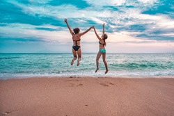 Carefree mother and daughter standing on the beach with arms outstretched